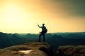 Strong hiker taking photo with smart phone at mountain peak. Marvelous daybreak.