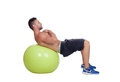 Strong man practicing abdominal on a big ball isolated white background Royalty Free Stock Images