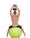 Strong man practicing exercises with dumbbells sit on a ball isolated white background Stock Images
