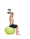 Strong man practicing exercises with dumbbells sit on a ball isolated white background Royalty Free Stock Photos