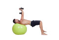 Strong man practicing exercises with dumbbells sit on a ball isolated white background Stock Photo