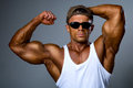 Strong man sunglasses shows his muscles Royalty Free Stock Photography
