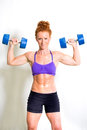 Strong muscular young woman lifting weights Royalty Free Stock Photo