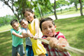 Strong team of four kids pulling the rope in the tug of war game Stock Photo