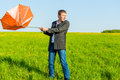Strong wind wrenched umbrella man orange Stock Images