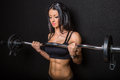 Strong woman an athletic and bodybuilder pumping up her muscles with barbell keeping her grace and femininity Stock Images