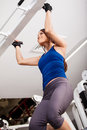 Strong woman doing bar pull ups very athletic young some at the gym shot from a low angle Stock Photography