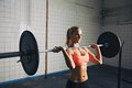 Strong woman lifting weights in crossfit gym fitness concentrating while barbells caucasian female model with Royalty Free Stock Photos