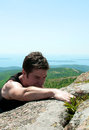 Strong young man climbing to the mountain top Stock Photography