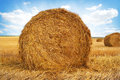 Stubble field and hay bales with under a spectacular summer sky Stock Images