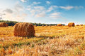 Stubble field with hay bales under a spectacular summer sky Stock Photos