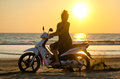 Stuck on the beach a girl a motorcycle in sand Stock Images