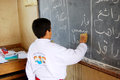 Student boy in classroom writing on blackboard arabic words and letters the using chalk to educate the poor Royalty Free Stock Photos