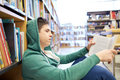 Student boy or young man reading book in library Royalty Free Stock Photo