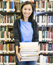 Student carrying books at the library young a heavy stack of Royalty Free Stock Photos