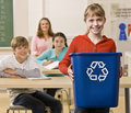 Student carrying recycling bin Stock Images