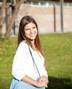 Student carrying shoulder bag on college campus side view portrait of smiling female Stock Photos