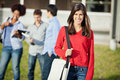 Student carrying shoulder bag on university campus portrait of beautiful college with friends in background Royalty Free Stock Photography