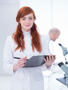 Student in a chemistry lab close up of smiling holding clip board around worktable with tools and her teacher analyzing Stock Image