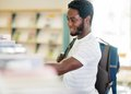 Student choosing book at library side view of young carrying backpack while Stock Photography