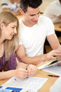 Student couple looking at tablet pc sitting in classroom and Royalty Free Stock Images