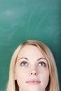 Student day dreaming while das oben gegen tafel schaut Stockfoto