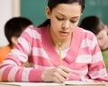 Student die in notitieboekje in schoolklaslokaal schrijft Stock Afbeelding