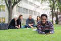 Student with digital tablet on grass at campus portrait of holding park friends studying in background Stock Photos