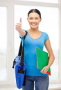 Student with folders and bags showing thumbs up education school concept smiling female bag at school Stock Photos