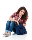 Student girl with bag sitting on floor isolated on white background Royalty Free Stock Photo