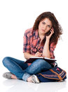 Student girl with bag sitting on floor and talking on cell phone Royalty Free Stock Photos