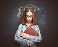 Student girl in cap, glasses and a book at blackboard Royalty Free Stock Photo
