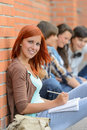 Student girl sitting outside campus with friends in row in background Stock Photo