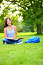 Student girl studying in park going back to school at university college happy sitting writing and reading Stock Images