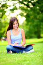 Student girl studying in park happy young asian adult sitting writing and reading outdoor on university campus mixed Royalty Free Stock Photography