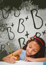 Student girl at table writing against green blackboard with school and education graphic Royalty Free Stock Photo