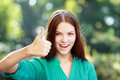 Student girl thumb up beautiful in green blouse lifts upwards against green of summer park Royalty Free Stock Image