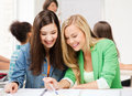 Student girls pointing at notebook at school Royalty Free Stock Photo