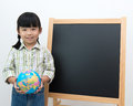 Student with globe and black board little girl holding school in front of the blackboard Royalty Free Stock Image