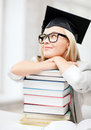 Student in graduation cap business and education concept happy with stack of books Royalty Free Stock Image