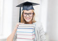 Student in graduation cap picture of happy with stack of books Stock Photo