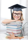 Student in graduation cap picture of happy with stack of books Stock Image