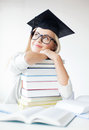 Student in graduation cap picture of happy with stack of books Royalty Free Stock Images