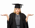 Student in graduation gown wondering what next portrait of college and mortar board shrugging against white background horizontal Royalty Free Stock Images