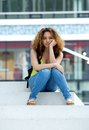 Student with grumpy expression portrait of a female sitting outside on face Royalty Free Stock Image