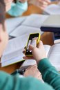 Student hands with smartphone making cheat sheet people education technology and exam concept close up of taking picture of books Royalty Free Stock Images