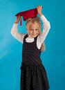A student with a hat schoolgirl in white tries on red Stock Images