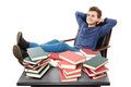 Student having a rest with the legs on the desk daydreaming amo studio shot of and hands under head among piles of books isolated Royalty Free Stock Photo