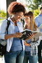 Student holding book while friend looking at her happy female in university campus Stock Photo