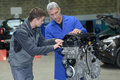 Student with instructor repairing car during apprenticeship